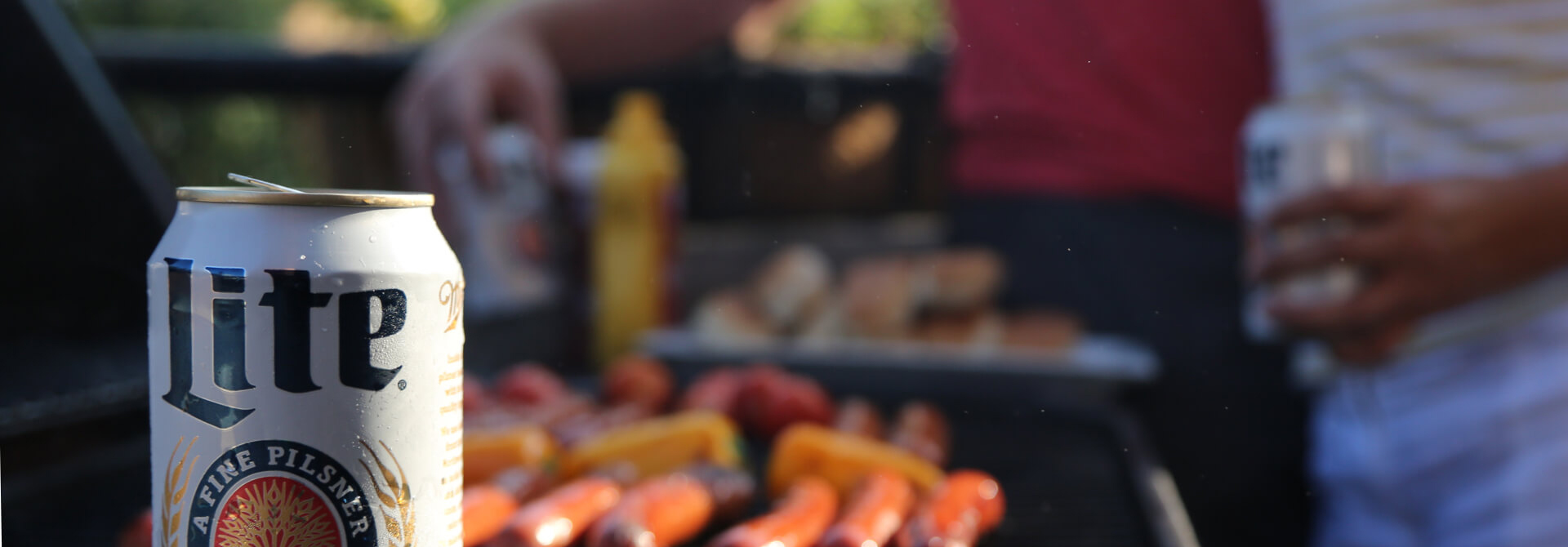 Miller Lite can and grill with sausages